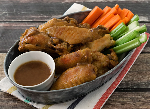 Instant Pot Teriyaki Chicken wings, ready to serve in a tin with carrots and celery and extra dipping teriyaki sauce