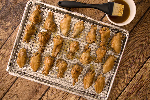 Shortcut Instant Pot wings  on a cooking rack ready to baste with sauce and go into the oven to broil