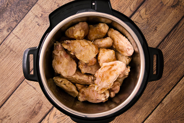Instant Pot Teriyaki chicken wings after sauteeing but before pressure cooking stacked inside an Instant Pot