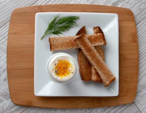 Soft-boiled egg in an egg cup plated with toast soldiers