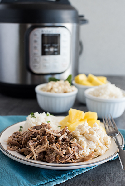 Instant Pot Kalua Pork recipe, plated and ready to serve with pineapple and macaroni and cheese and white riice