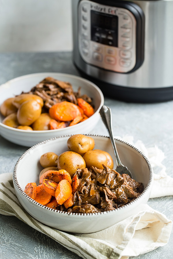 two bowls of Old-Fashioned Pot Roast in front of an Instant Pot.