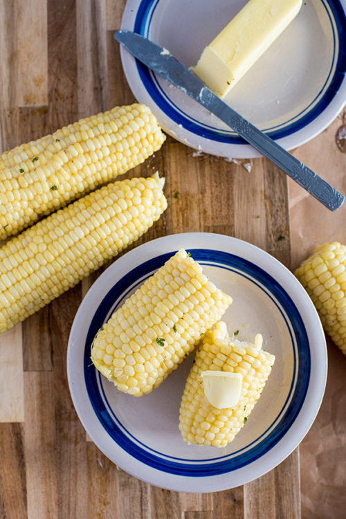 Corn on the cob cooked in the pressure cooker, plated and topped with butter, salt, and pepper
