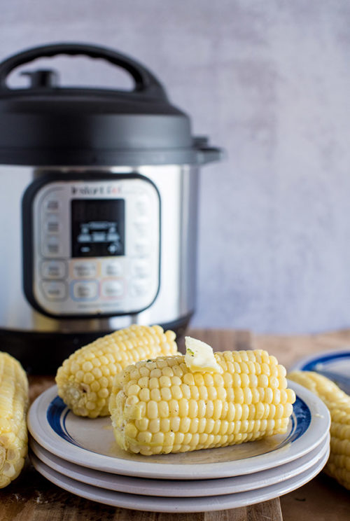 Corn on the Cob, plated and drizzled in butter, with an Instant Pot in the background