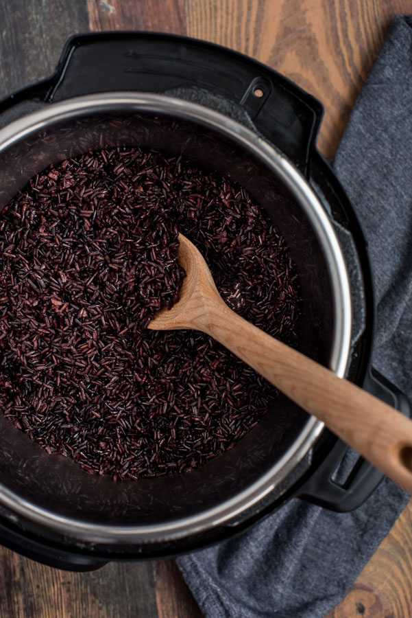 Black rice after pressure cooking in the Instant Pot, inside the cooking pot with a wooden spoon for stirring