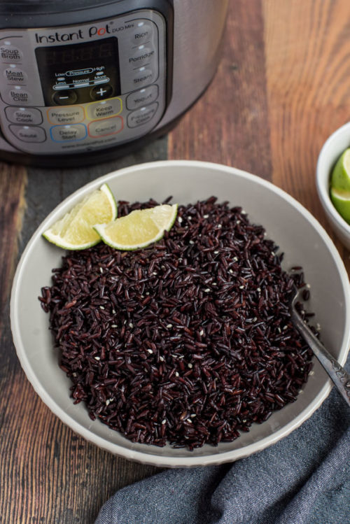 A white bowl full of Pressure Cooker Black Rice, shot from above, with an Instant Pot and limes in the background