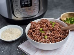Pressure Cooker Pink Rice prepared with sesame seeds, chopped green onions, and an Instant Pot in the background