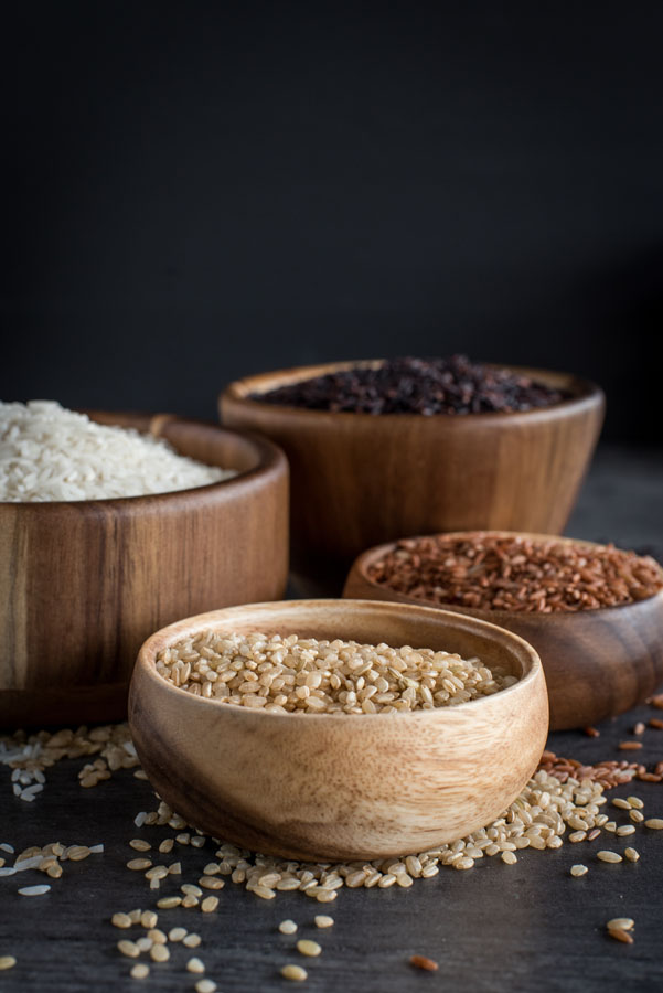 A side profile shot of four wooden bowls of different types of rice