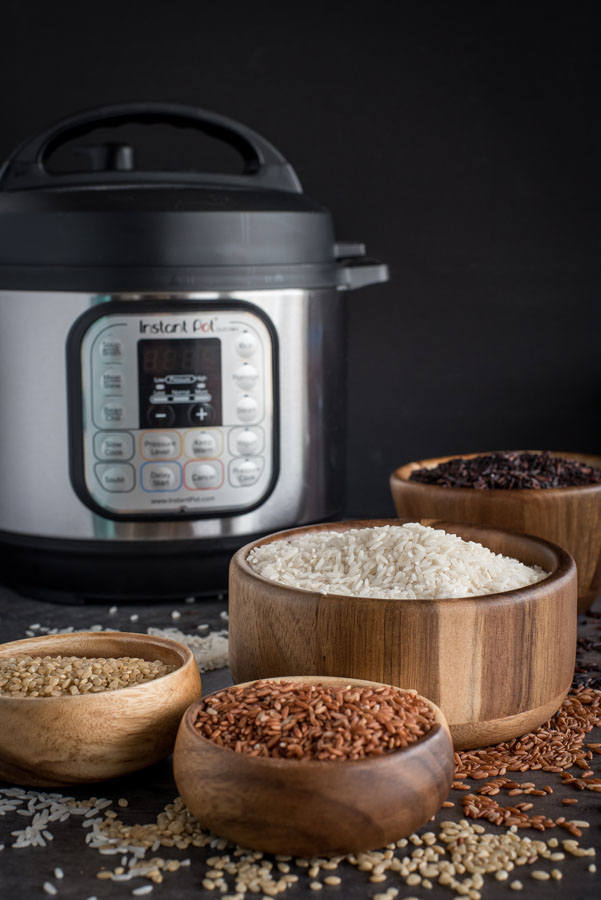 Four wooden bowls of different types of rice with an Instant Pot in the background