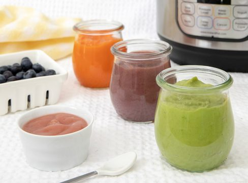 Different colors of Instant Pot baby food puree with an Instant Pot and fresh fruit in the background