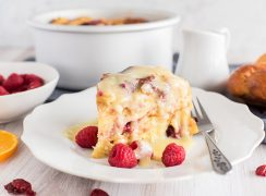 Pressure Cooker Raspberry Orange Bread Pudding, dished up with the cake pan and bowl of raspberries in the background