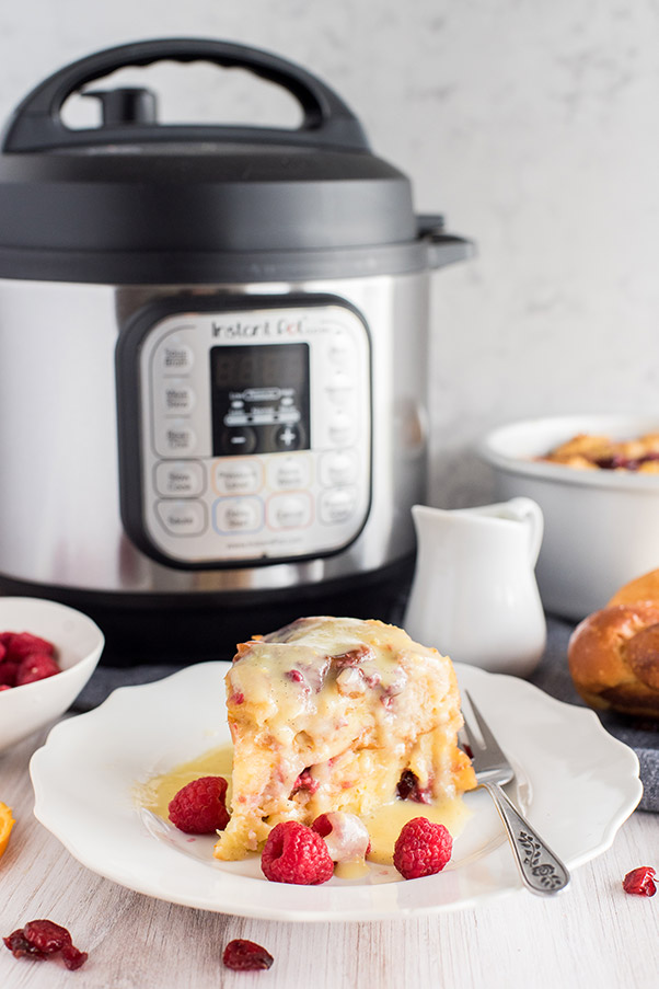 Instant Pot Raspberry Bread Pudding on a plate with Instant Pot in the background.