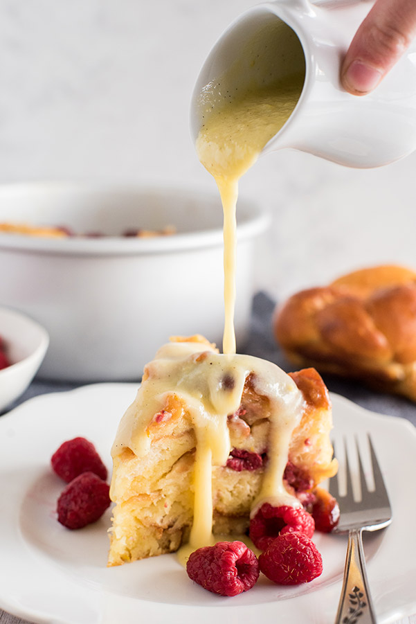 A close up of raspberry orange bread pudding  on a plate being drizzled with cream cheese frosting