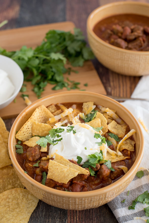 A yellow bowl of Easy Pressure Cooker Chili, topped with sour cream, cheese, cilantro, and tortilla chips