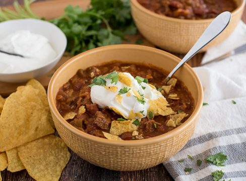 Beef and Bean Instant Pot Chili, dished up in a yellow serving bowl, with tortilla chips, sour cream, cheddar cheese, and cilantro