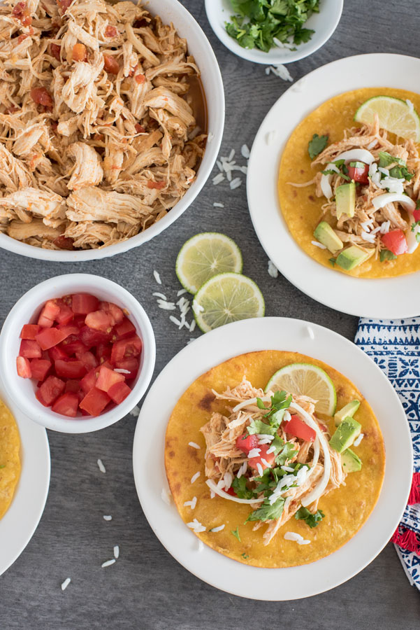 An overhead shot of shredded chicken tacos pressure cooker, with diced tomatoes, cilantro, limes, and additional Instant Pot shredded chicken taco filling
