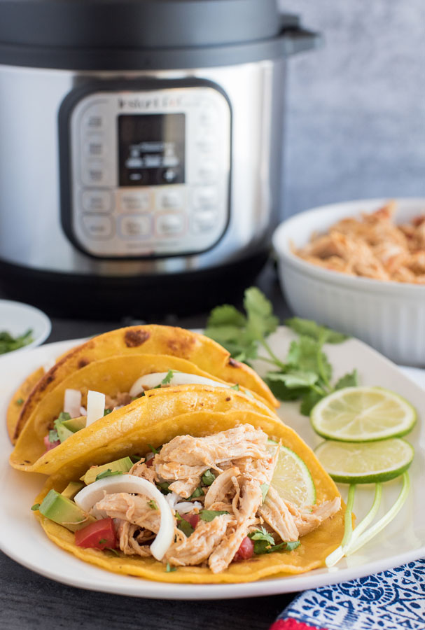 Three Pressure Cooker Chicken Tacos plated with a garnish of cilantro and limes, with an Instant Pot and a bowl of shredded chicken taco meat in the background