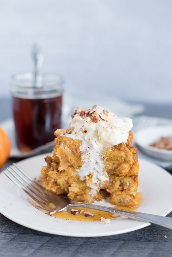 Profile view of Instant Pot / Pressure Cooker Pumpkin Spice Baked French Toast recipe with maple syrup in the background.
