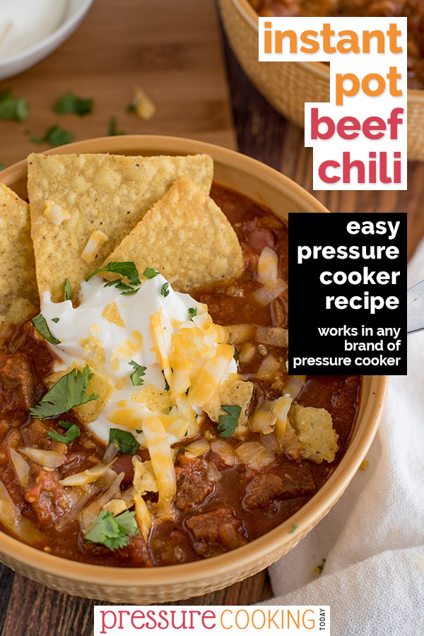 Pin It Now: Instant Pot Beef Chili, dished up in a yellow serving bowl, topped with tortilla chips, sour cream, cheddar cheese, and cilantro