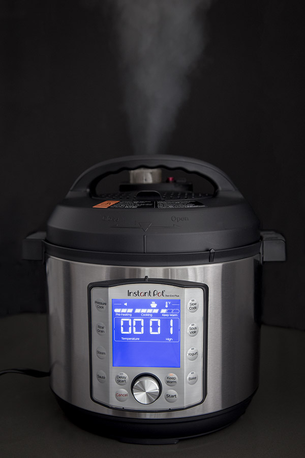 Instant Pot Evo Duo Plus quick release showing with a jet of steam coming out against a black background