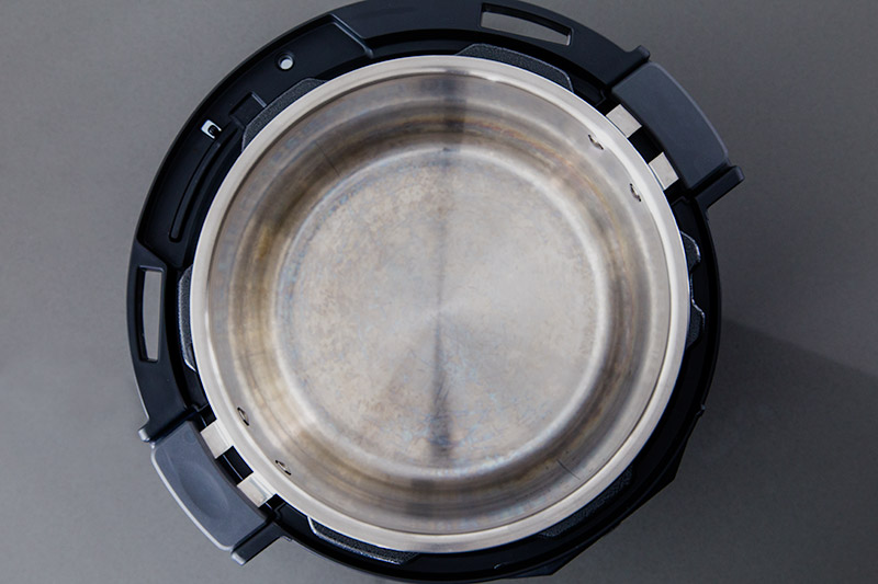 An overhead view of the Instapot Evo Plus inner cooking pot with handles viiable inside the housing