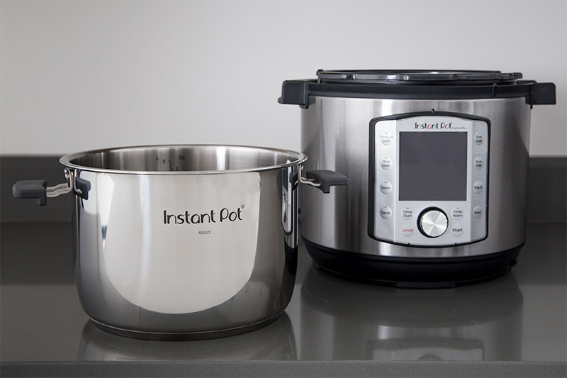 Instant Pot Evo inner pot with handles next to pressure cooker housing.