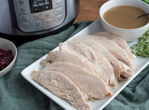 A rectangle plate of Pressure Cooker Thanksgiving Turkey recipe, with and Instant Pot, gravy, and cranberries in the background