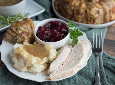 A plate of sliced turkey, mashed potatoes, stuffing and cranberry sauce