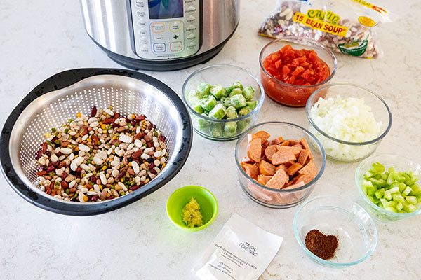 An Instant Pot in the background with, Cajun 15 beans mix, okra, sausage, celery, onion, and seasonings