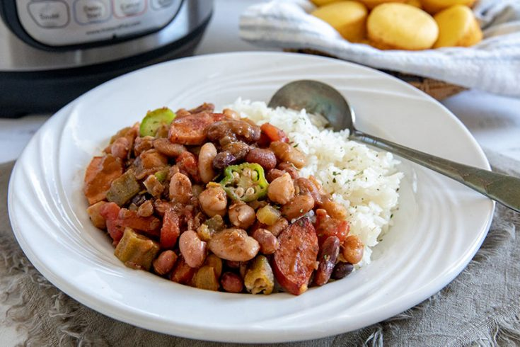 A bowl of Cajun 15 Bean Soup with sausage served over white rice
