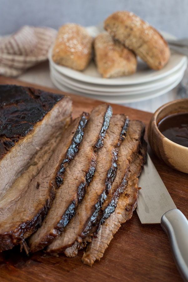 BBQ beef brisket cooked in an Instant Pot sliced on a cutting board with rolls in the back ground.