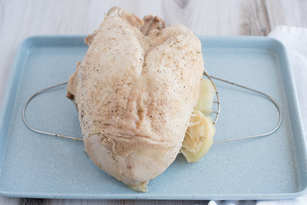 Fully cooked pressure cooker turkey breast resting on a baking tray.