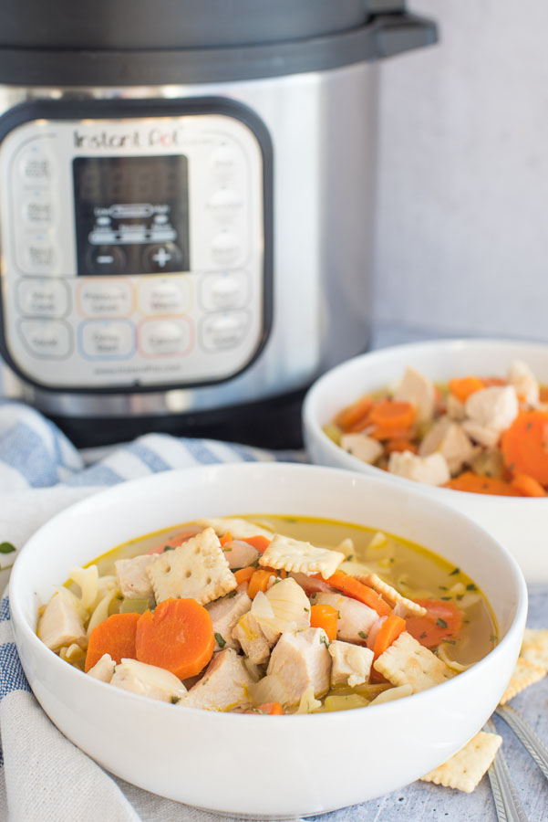 Best Pressure cooker chicken noodle soup dished up in a white serving bowl with a second bowl and an Instant Pot in the background.