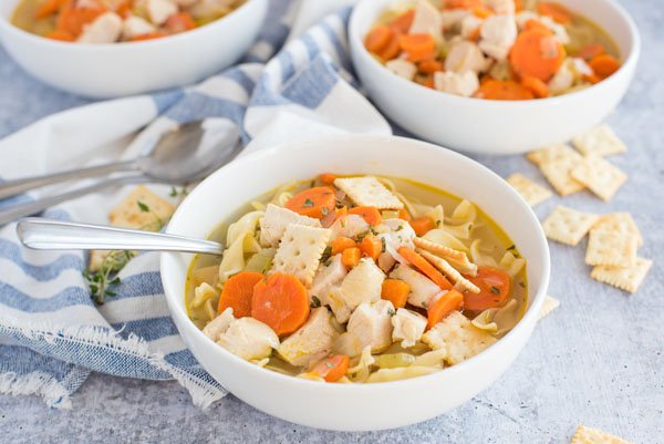 Instant Pot chicken noodle soup served in a bowl with crackers.