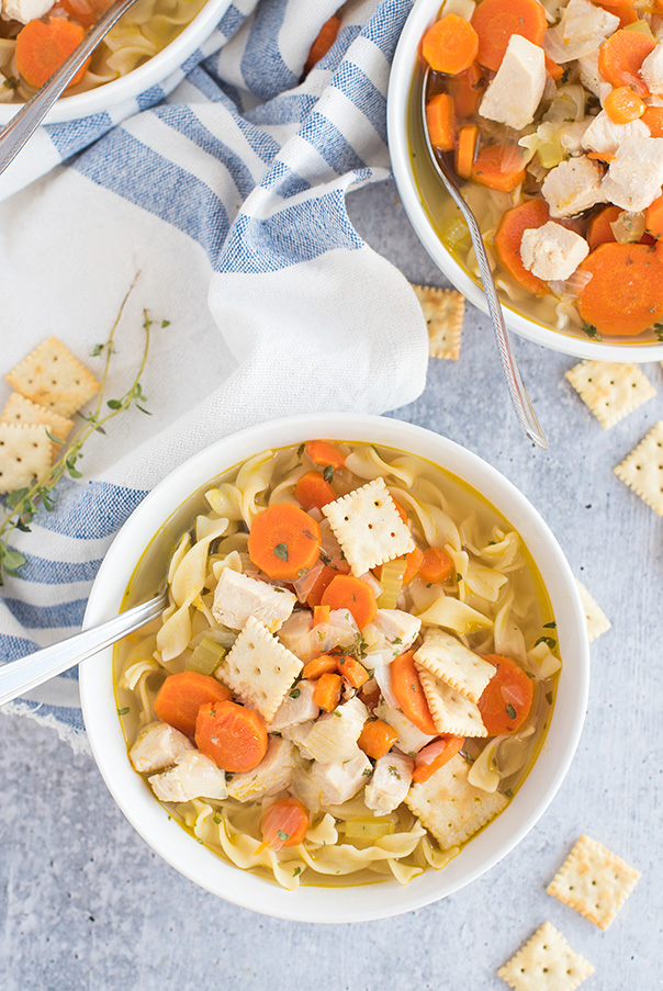 Pressure cooker chicken noodle soup served in a bowl and topped with crackers.