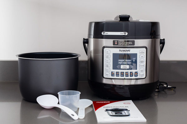 NuWave Pressure Cooker with a non-stick inner pot, ladel, rice scoop, measuring cup, and manual.