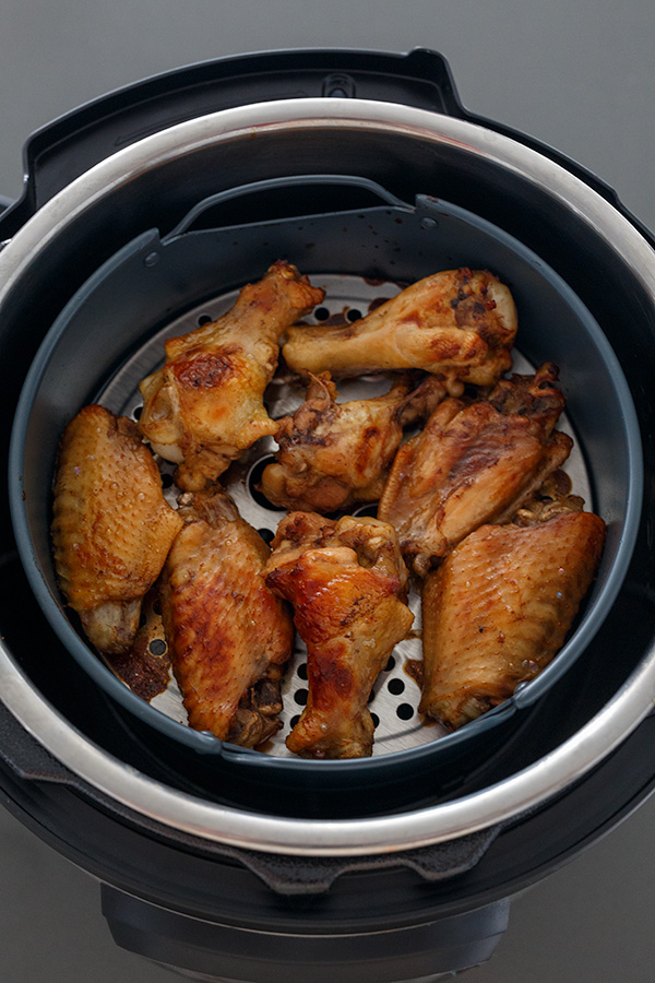 Teriyaki chicken wings browned up with the Instant Pot Air Fryer Lid in an air fryer basket.