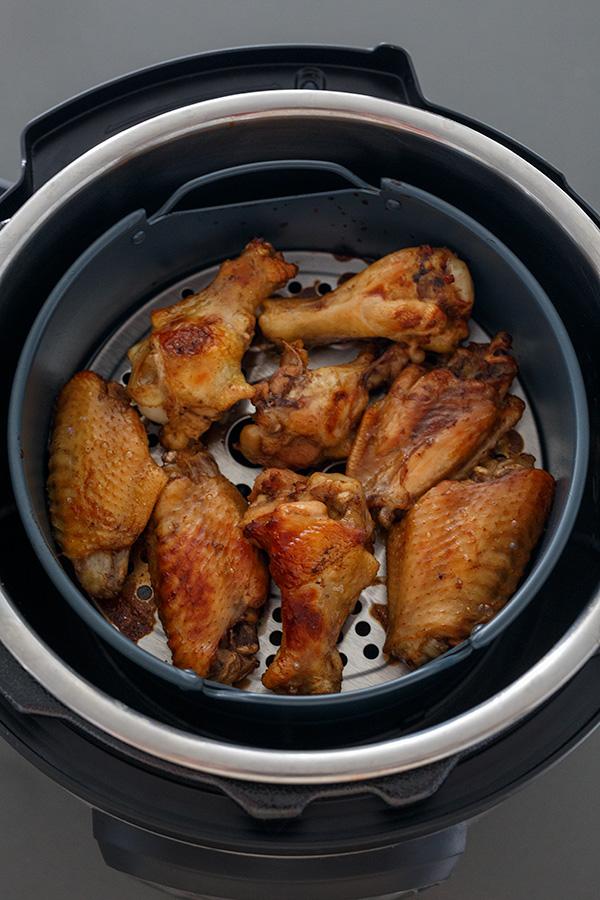 Teriyaki chicken wings browned up in an air fryer basket.