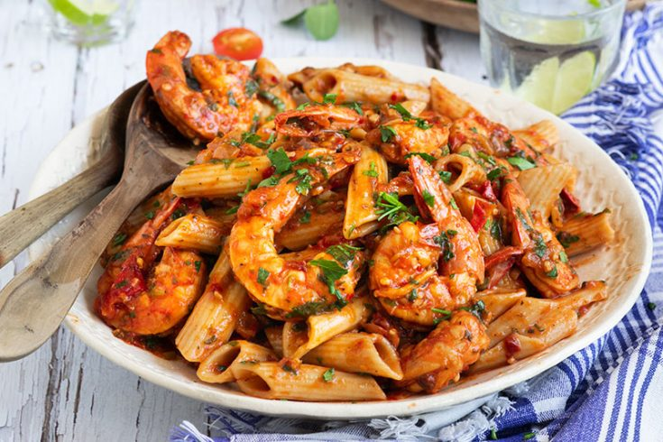 Close up on a large white serving plate of pressure cooker / Instant Pot Shrimp Fra Diavlo over penne pasta topped with fresh parsley.