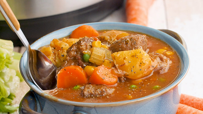 A bowl of pressure cooker beef stew ready to serve with a spoon.
