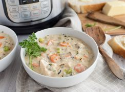 White bowl of creamy pressure cooker chicken wild rice soup garnished with parsley in front of an Instant Pot with white bread and a wooden spoon.