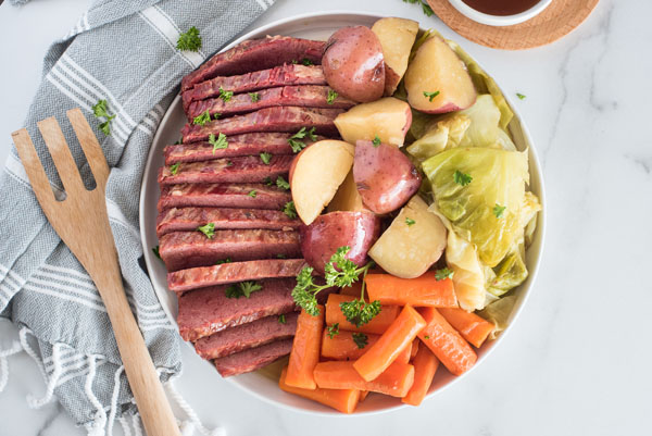 Corned Beef and Cabbage on a white circular serving dish with a wooden spoon resting on a grey and white linen napkin.