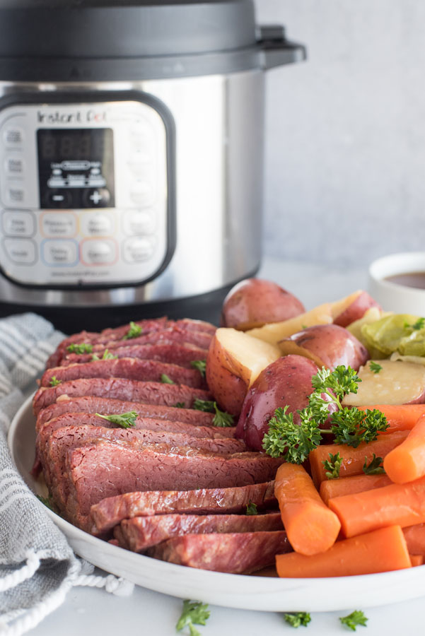 Side view of pressure cooker Corned Beef, cabbage, potatoes and carrots on a white serving platter with an Instant Pot in the background.