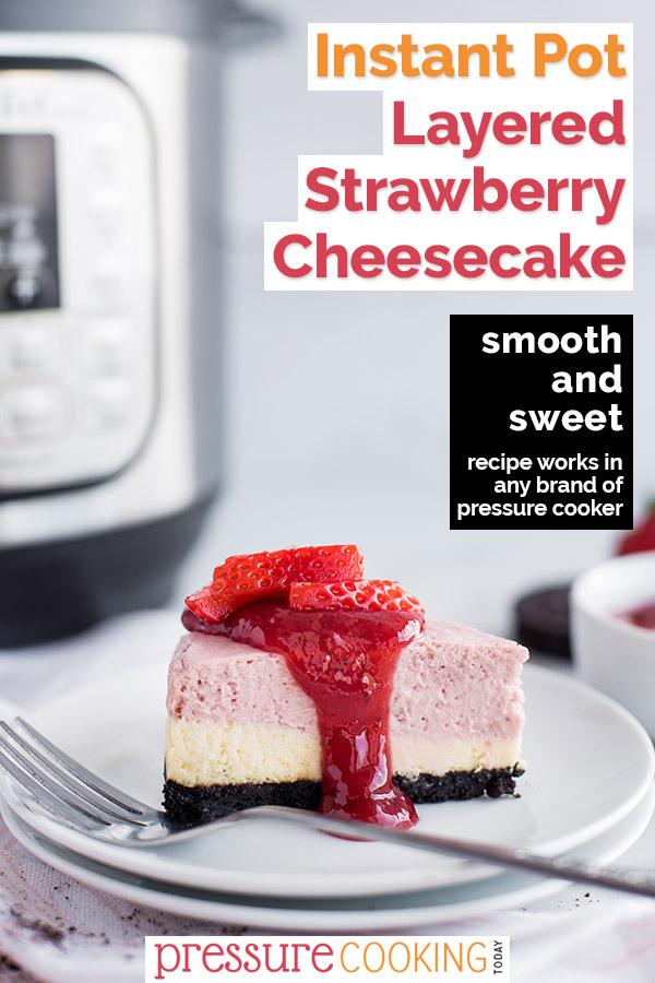 A slice of pink and white layered cheesecake topped with strawberries placed in front of an Instant Pot.