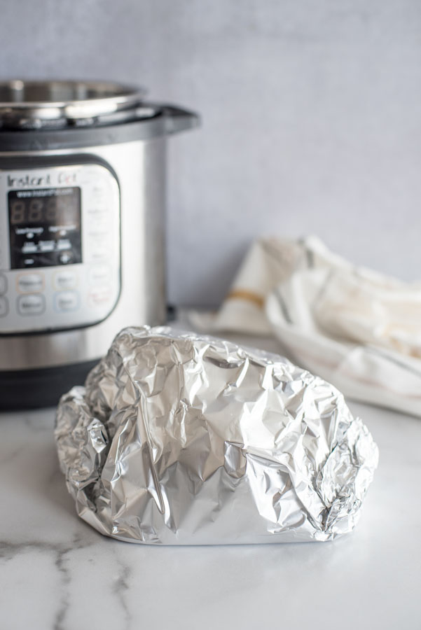 Ham wrapped in aluminum foil to be heated in the Instant Pot / pressure cooker on a marble counter with a white cloth in the background.