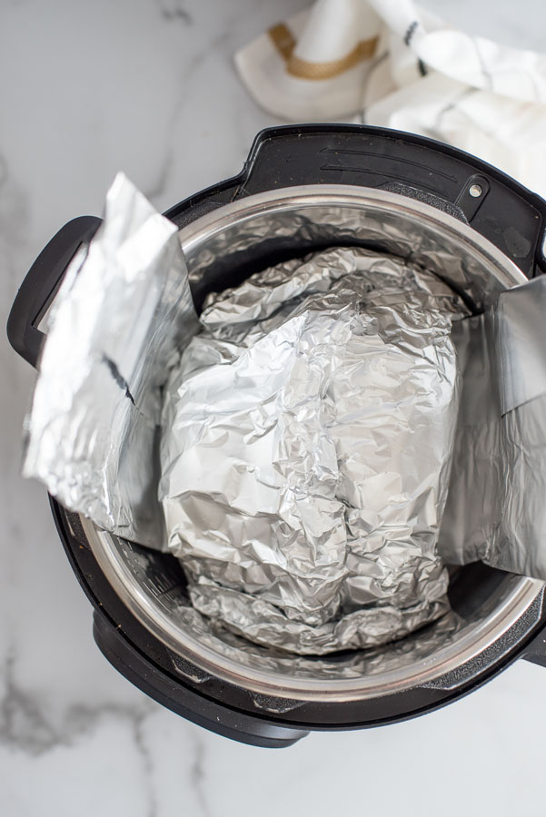 Overhead of spiral ham wrapped in aluminum foil inside an instant pot with a tin foil sling.