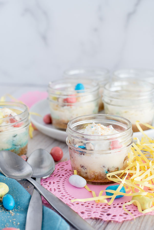 Side view of multiple mini Robin Egg Cheesecakes baked in a pressure cooker in individual glass mason jars for Easter.