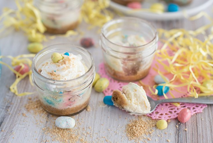 Side view of two mini pressure cooker Robin Egg's Cheesecake made in mini glass mason jars with Whoppers Robin Eggs on a white wooden table decorated for Easter.