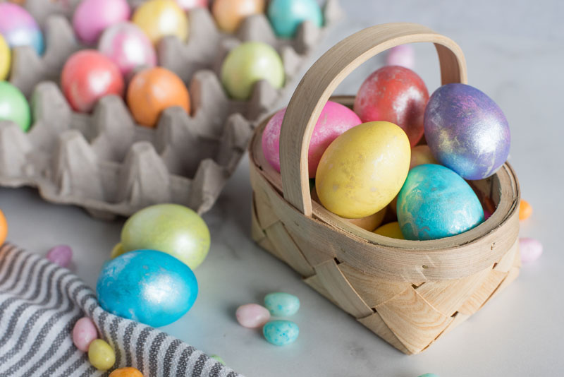 Easter eggs made in an Instant Pot and placed in a basket in front of a carton of Easter eggs.