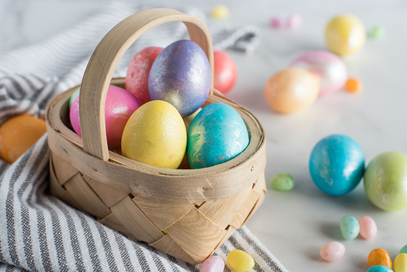 Pressure cooker hard boiled eggs dyed for Easter and placed in a basket with dyed eggs and jellybeans around it.
